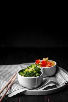 Брокколи в чашке с палочками для еды и болгарским перцем