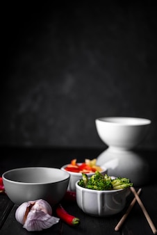 Вид спереди чашки овощей с чесноком