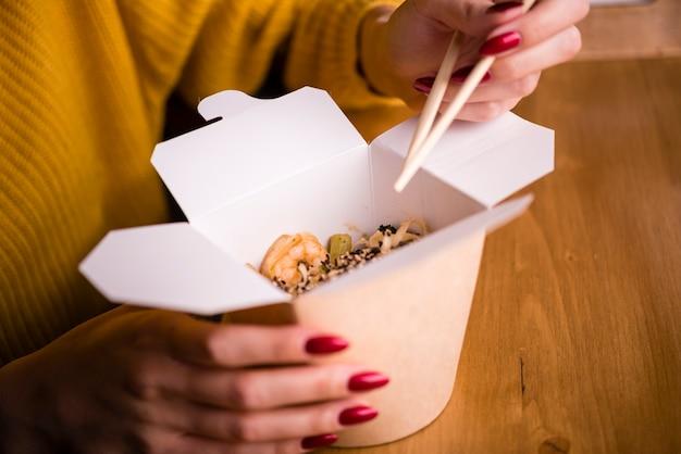 Женщина держит палочки для еды и коробку с лапшой