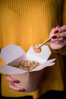 Женщина, держащая коробку с лапшой и креветками