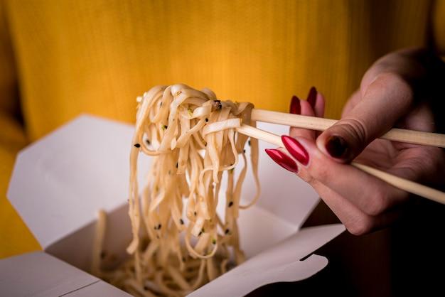 Женщина, держащая палочки для еды с лапшой