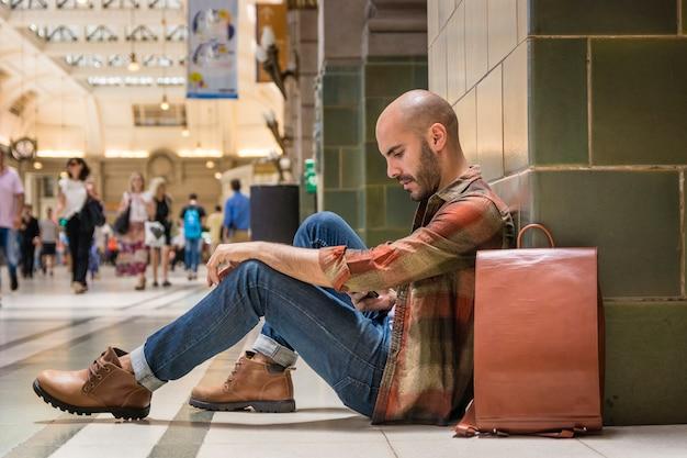 地下鉄の床に座っている旅行者