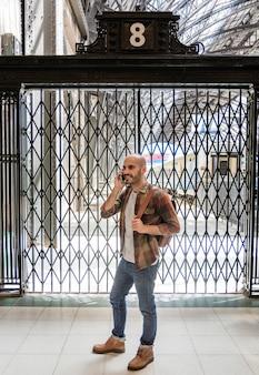 電話で話しているバックパックを持つ男