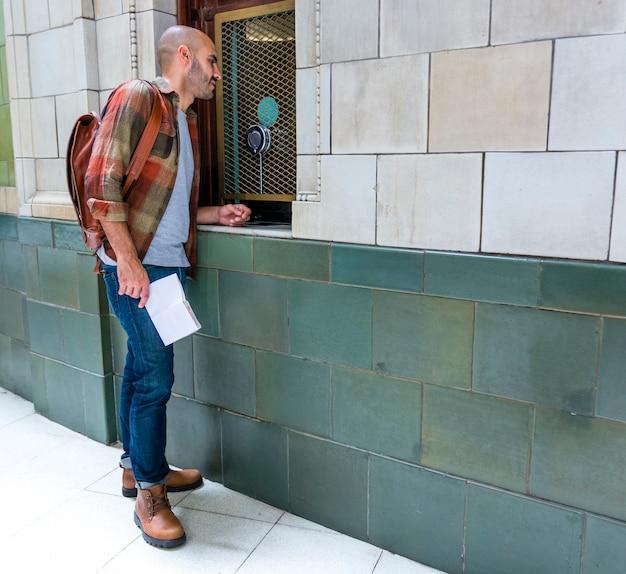 街の景色をチェックするバックパックを持つ男