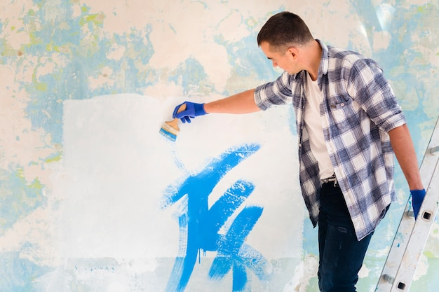 壁を塗る男のミディアムショット