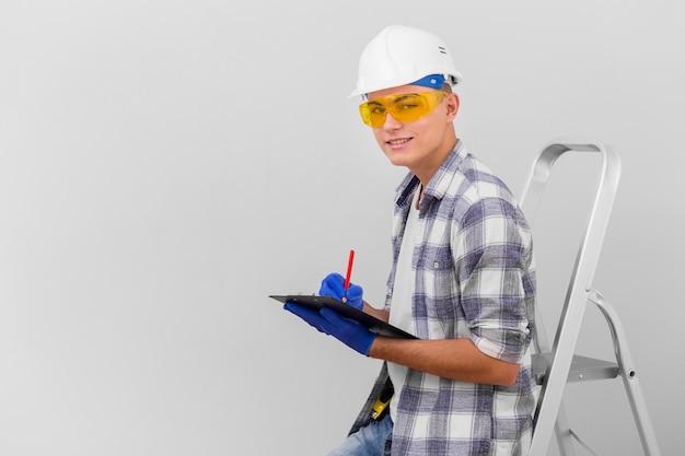 Молодой человек держит буфер обмена на лестнице