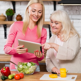 Дочь держит цифровой планшет и мать прокручивает