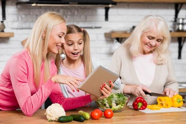 おばあちゃんは料理をしていて、女性はタブレットを使っています