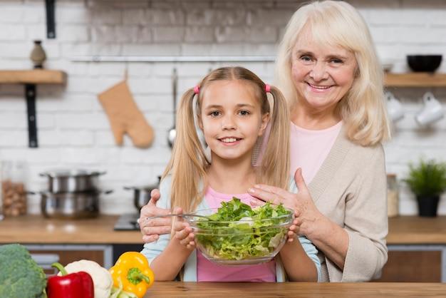 祖母と孫娘のサラダを保持