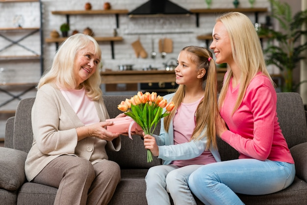 おばあちゃんに花の花束を提供する孫娘