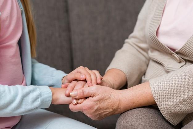 祖母と孫娘の手のクローズアップを保持