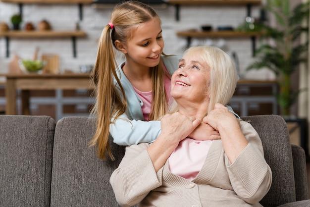 祖母と孫娘がお互いのミディアムショットを見て