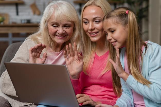 ノートパソコンの前で手を振っている女性