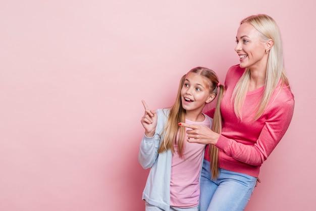 Мать и дочь, глядя в сторону и скопировать космический фон