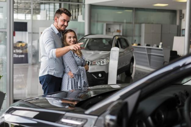 Мужчина показывает своей девушке автомобиль