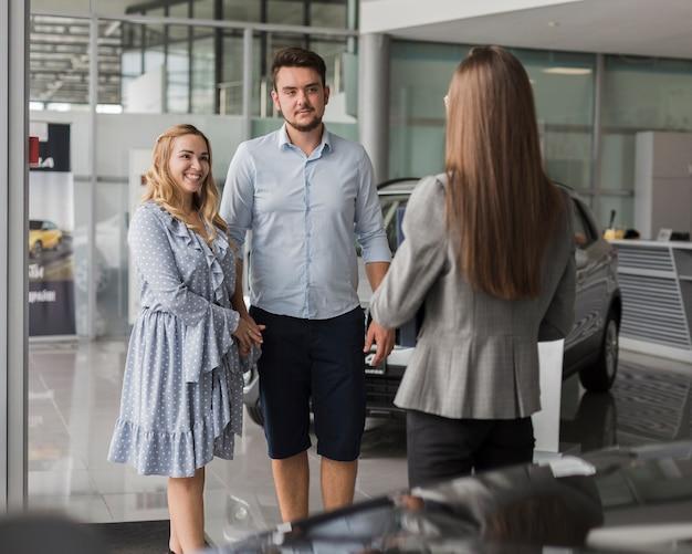 Молодая пара разговаривает с агентом автосалона