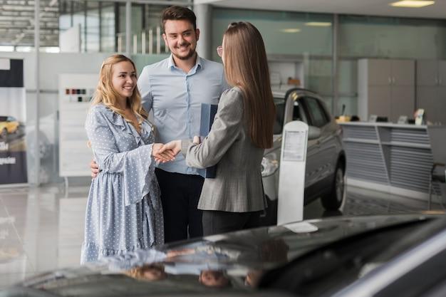 Счастливая пара разговаривает с агентом автосалона