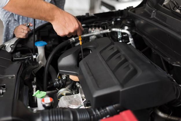 男性の手が車のエンジンをチェック