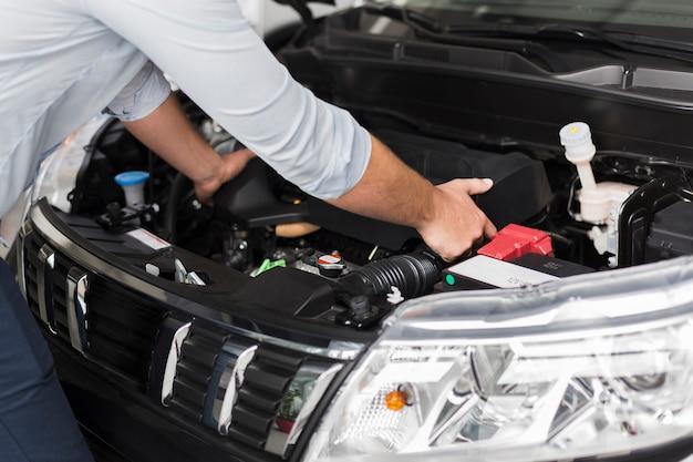 車のエンジンを取り出す男性の手
