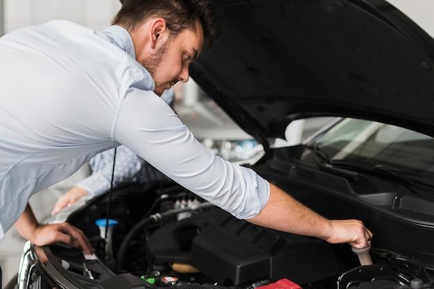 車のエンジンを検査するハンサムな男