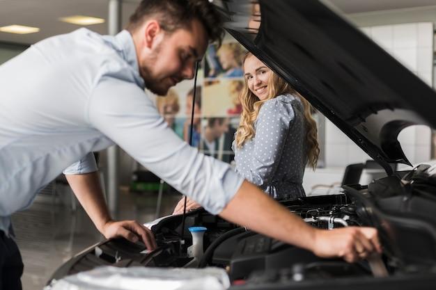 Боковой вид мужчина осматривает двигатель автомобиля