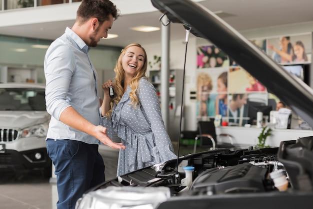 笑顔の女性に車のエンジンを示す男