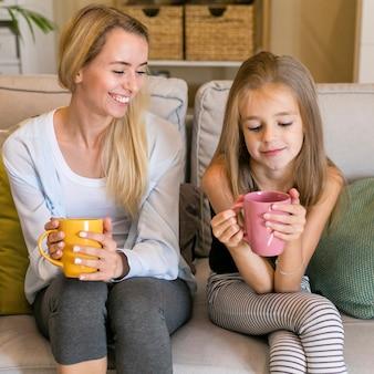 母は彼女の子供に笑顔とマグカップを保持