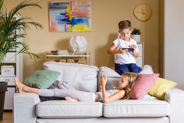 リビングルームで自分の携帯電話を見ている兄と妹