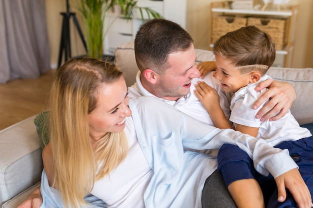 幸せな親が息子を押しながらリビングルームに座っています。