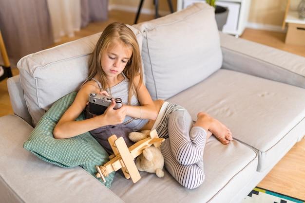 Девушка смотрит на старую камеру и сидит на диване