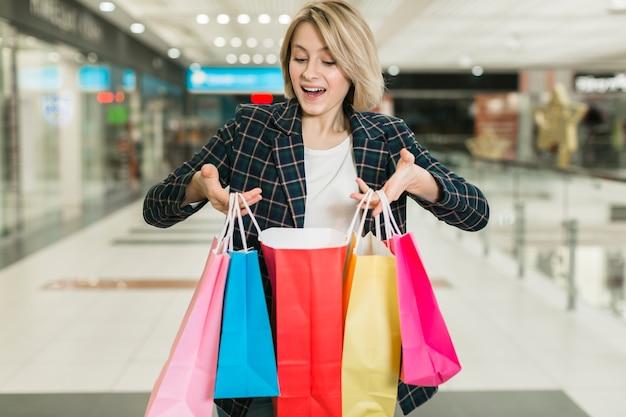 Счастливая взрослая женщина держа хозяйственные сумки