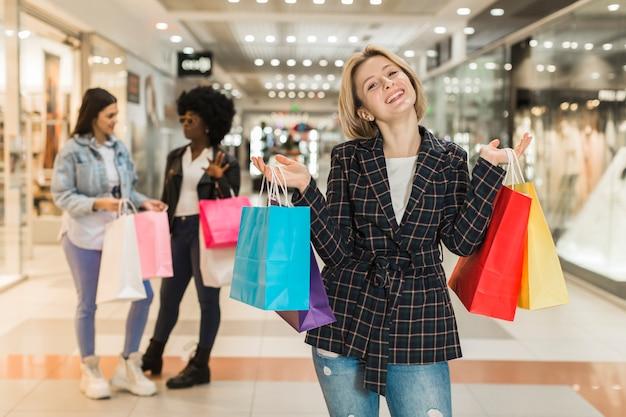 Вид спереди женщина покупками с друзьями