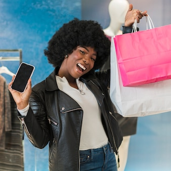 Портрет счастливой женщины, держащей ее сумки