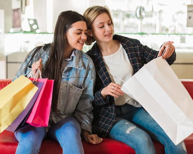 Молодые женщины проверяют сумки
