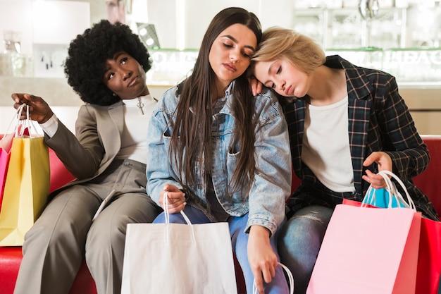 Группа женщин устала после покупок