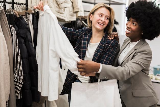 Счастливые друзья покупают одежду