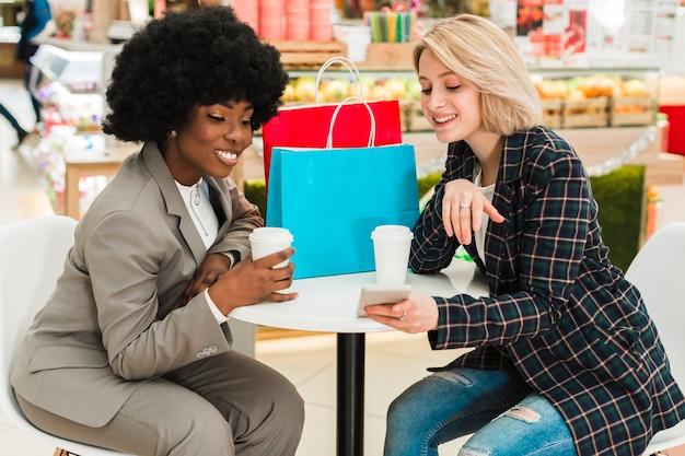 Женщина показывает что-то своему другу по телефону