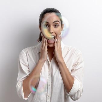 ミディアムショットびっくり石鹸の風船を持つ女性