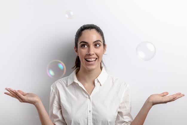 Вид спереди женщины, улыбаясь с позирует с пузырьками