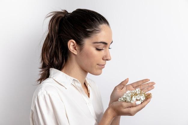Вид сбоку женщины с цветами в руках