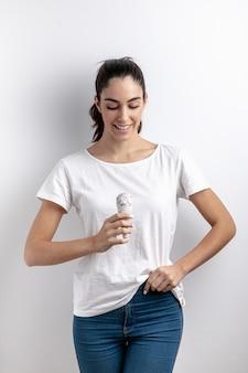 アイスクリームコーンを保持している笑顔の女性の正面図