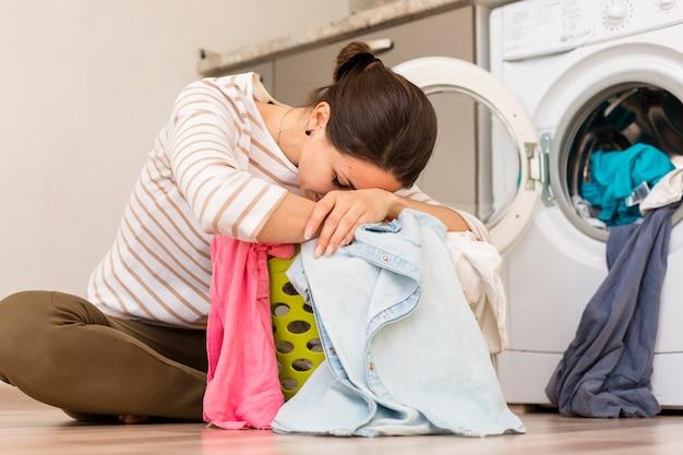 Измученная женщина стирает белье