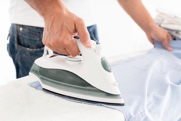 Неузнаваемый мужчина гладит одежду