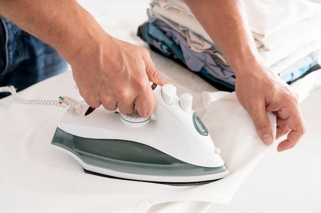 Мужчина гладит одежду, вид сбоку