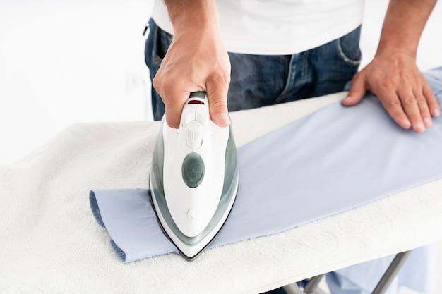 Человек гладит костюм рубашку крупным планом