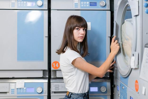 Женщина закрывает дверь стиральной машины