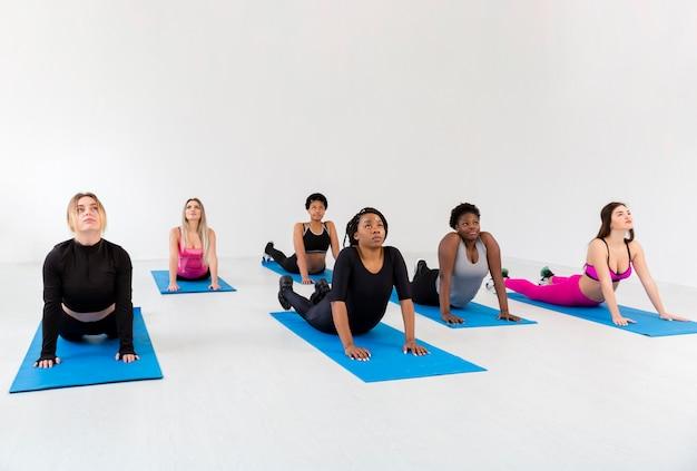 Женщины высокого угла на уроке фитнеса