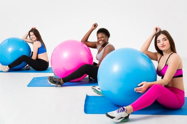 Женщины на уроке фитнеса тренируются на коврике