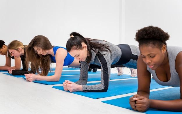 Женщины делают упражнение на сопротивление на коврике