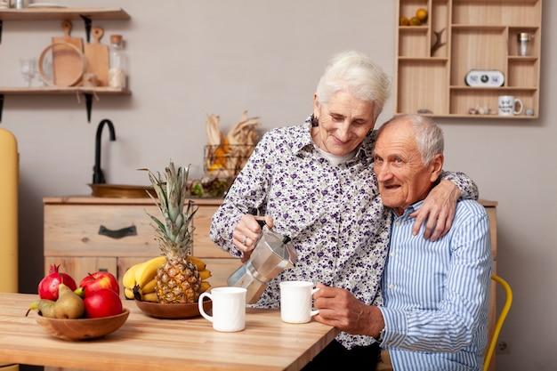 台所でコーヒーを飲んでいる年配のカップル